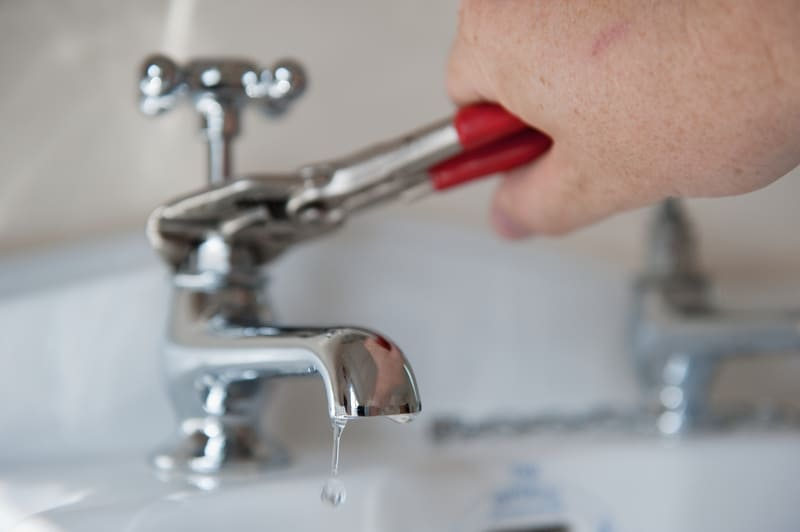 Technician fixing sink faucet with plair